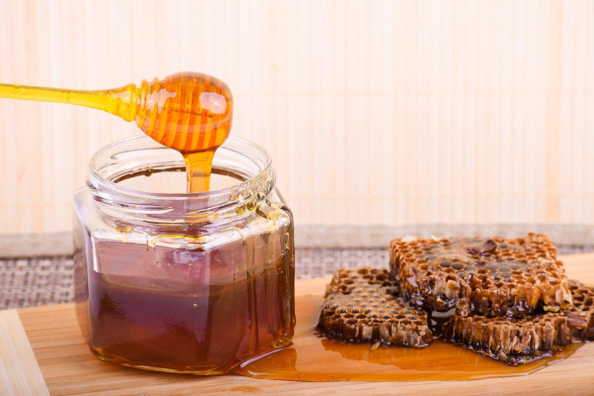 Cuillère dans un pot transparent avec du miel coulant sur les alvéoles