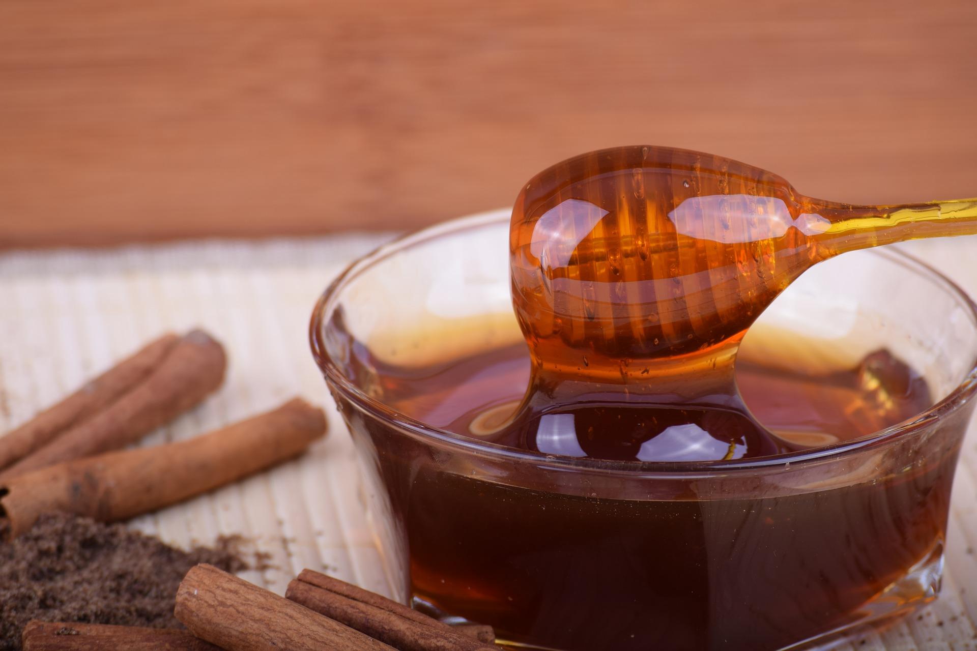 Cuillère dans un pot de miel transparent avec de la cannelle en bâtons et moulue